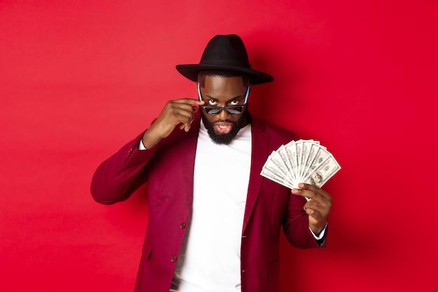 Hombre negro atrevido y fresco con sombrero y traje de fiesta, mostrando dólares y mirando por debajo de las gafas de sol, de pie sobre un fondo rojo.