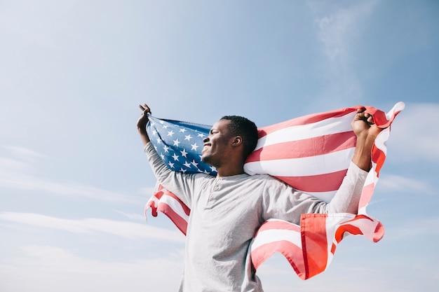 Hombre negro con bandera americana que simboliza la libertad.