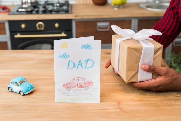 Hombre negro con caja de regalo cerca de tarjeta de felicitación