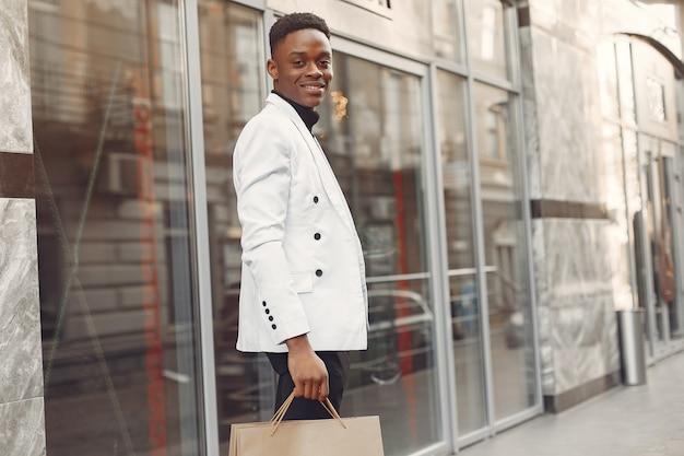Hombre negro con una chaqueta blanca con bolsas de compras