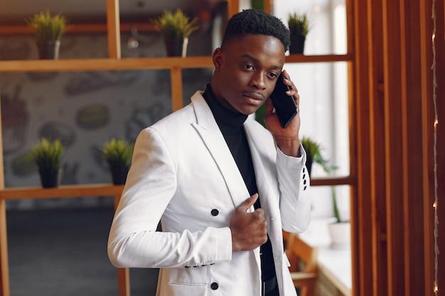 Hombre negro en una chaqueta blanca de pie con un teléfono