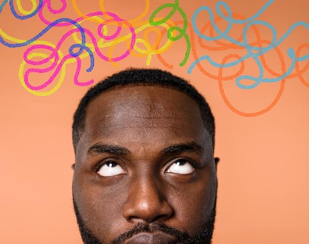 El hombre negro confundido tiene que elegir la flecha derecha a seguir. concepto de opciones, confusión, decisión.