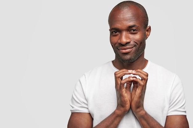 El hombre negro curioso mantiene las manos en un gesto intrigante, se ve con gran interés, tiene la intención en mente, usa una camiseta blanca informal