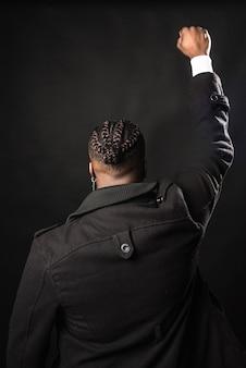 Hombre negro por detrás con el puño levantado. tiro medio. fondo negro.