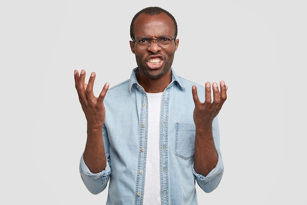 Hombre negro enojado enojado grita y sacude las palmas, harto de discutir, aprieta los dientes