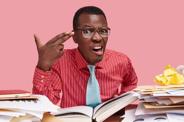 El hombre negro estresante hace un gesto de suicidio, tiene una expresión facial insatisfecha