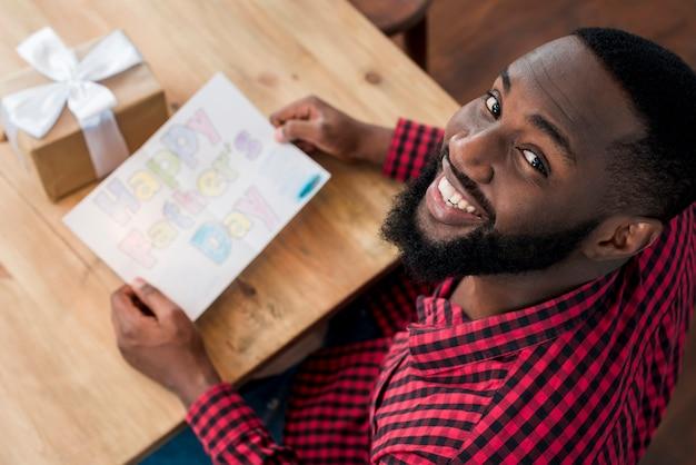 Hombre negro feliz que sostiene la tarjeta de felicitación