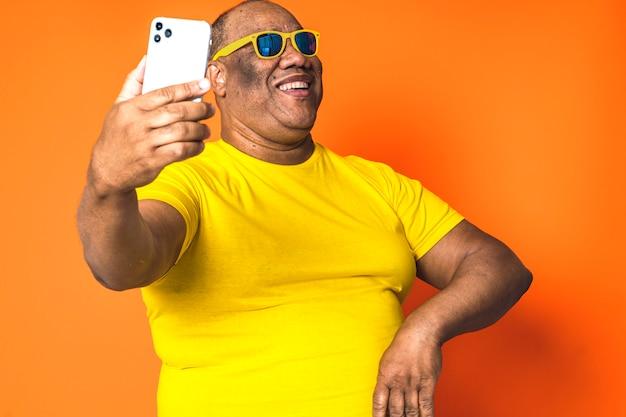 Hombre negro feliz que usa el teléfono móvil en fondo aislado. concepto de tecnología y comunicaciones en personas mayores