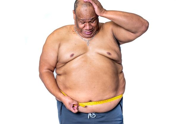 Un hombre negro y gordo mide su cintura con una cinta métrica para ver si ha perdido peso con el régimen