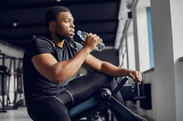 Un hombre negro guapo se dedica a un gimnasio
