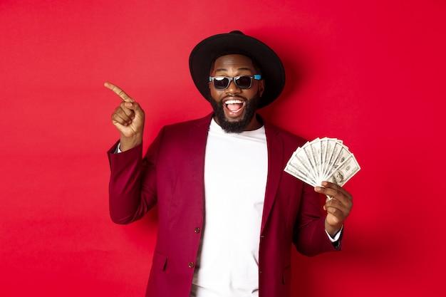 Hombre negro guapo y elegante apuntando con el dedo hacia la izquierda mientras muestra dinero, sosteniendo dólares y mostrando el logotipo, de pie sobre fondo rojo