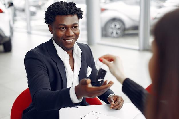 Hombre negro guapo y elegante en un salón del automóvil