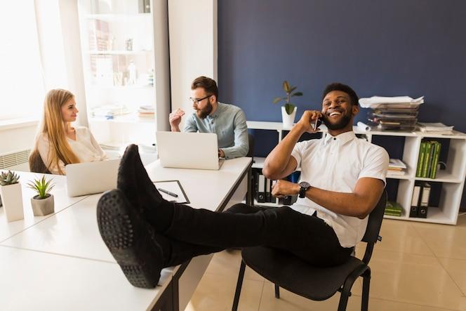 Hombre negro hablando por teléfono en la oficina