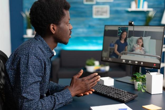 Hombre negro hablando con su familia en la sala de hospital utilizando videollamada de teleconferencia en línea de intenet para ...