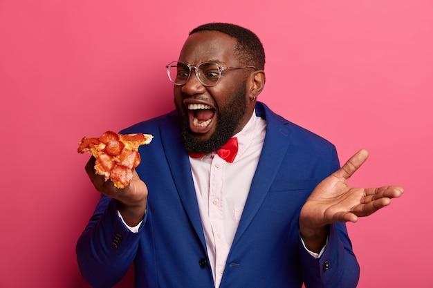 El hombre negro hambriento muerde un trozo de pizza muy grande, tiene apetito, usa ropa formal y posa ante un espacio rosa