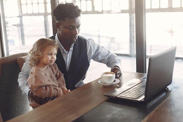 Hombre negro con hija blanca de pie en un café