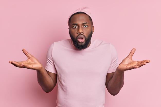 El hombre negro indeciso confundido conmocionado extiende las palmas de las manos desconcertado por la situación difícil, parece sorprendido e inconsciente usa una camiseta con sombrero aislada sobre una pared rosa
