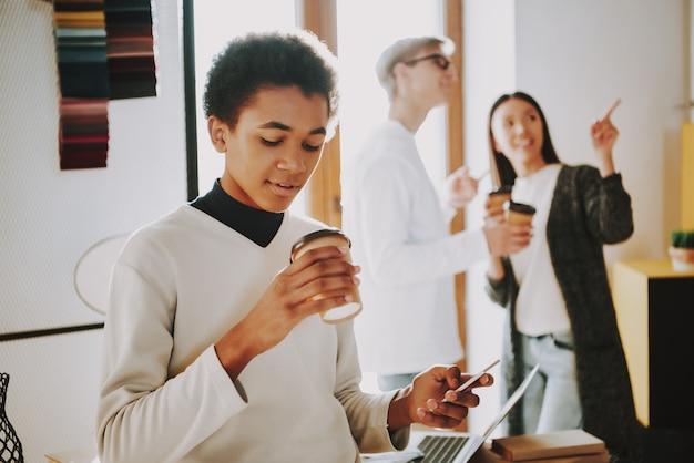 Hombre negro joven bebe cafe en lugar de coworking