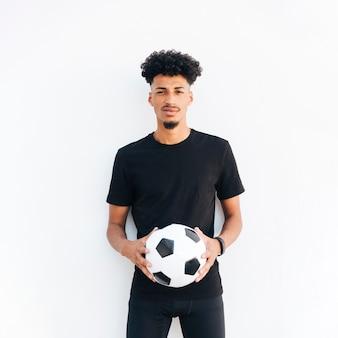 Hombre negro joven con la bola que mira la cámara