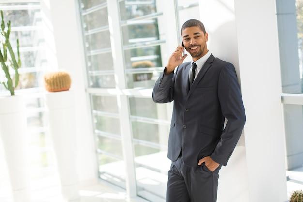 Hombre negro joven hermoso con el teléfono móvil en la oficina