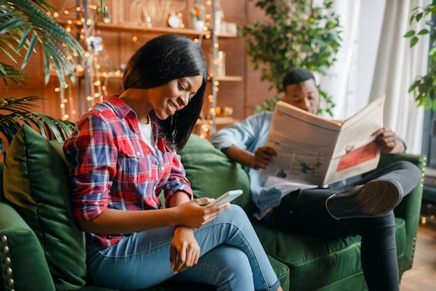 Hombre negro leyendo el periódico, su mujer con teléfono