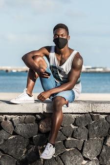 Hombre negro en máscara y con smartphone en la orilla del mar