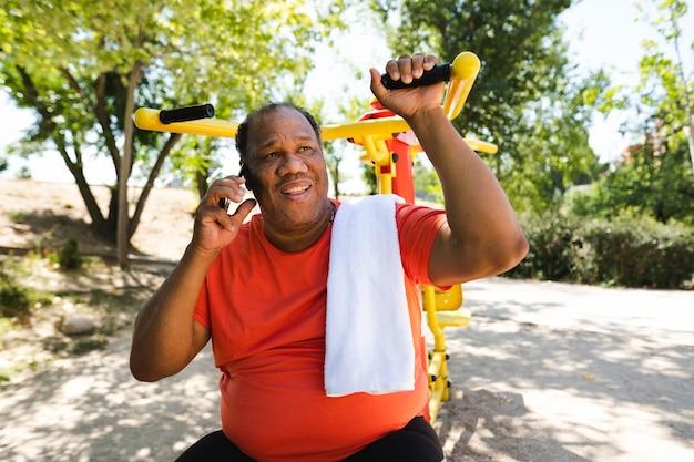 Hombre negro mayor realiza ejercicios para perder peso al aire libre y habla por teléfono