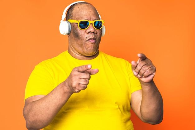 Hombre negro mayor sensación joven feliz bailando escuchando música en sus auriculares y con gafas de sol en la cara. concepto de tecnología en personas mayores
