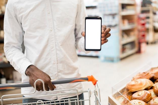 Hombre negro mostrando teléfono inteligente en tienda de comestibles