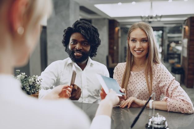 Hombre negro y mujer caucásica check-in en la recepción del hotel