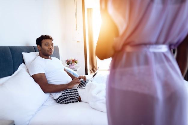 Hombre negro y mujer sexy en el dormitorio.