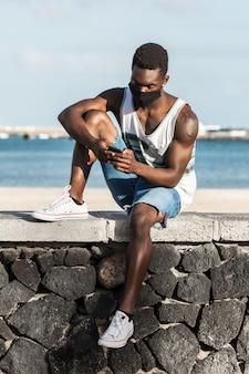 Hombre negro navegación smartphone en valla de piedra contra la orilla del mar