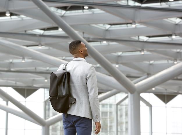 Hombre negro parado solo en el aeropuerto con bolsa