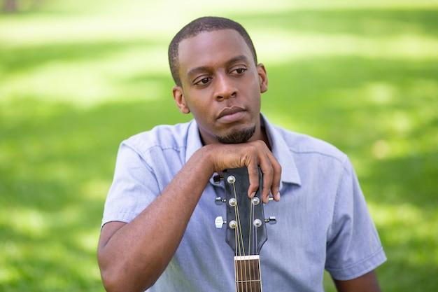 Hombre negro pensativo apoyado en cabezal de guitarra en el parque