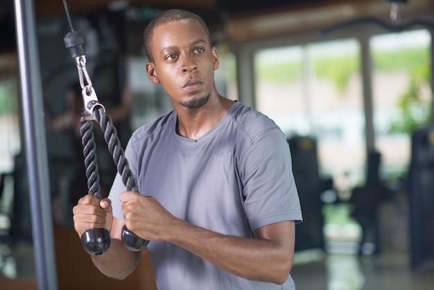 Hombre negro pensativo que usa el equipo del gimnasio y que mira lejos