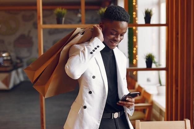 Hombre negro de pie en un café con bolsas de compras