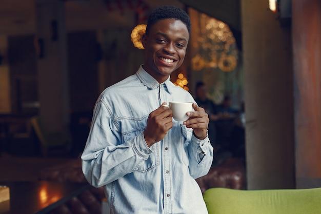 Hombre negro de pie en una cafetería y tomando un café