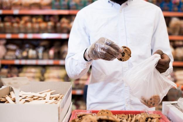 Hombre negro poniendo galletas en una bolsa de plástico en la tienda de comestibles
