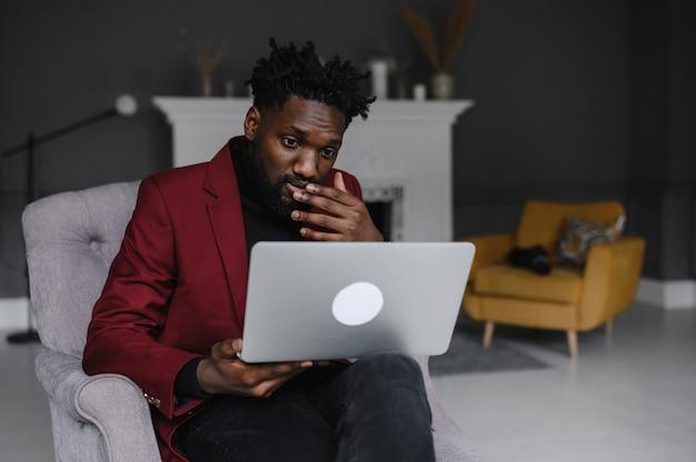 Hombre negro que trabaja desde casa con videoconferencia grupal en línea en portátil