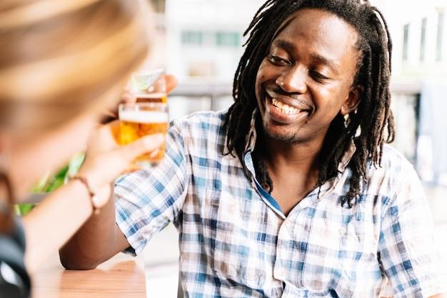 Hombre negro con rastas brindando con una cerveza