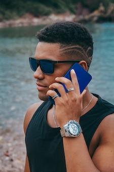 Hombre negro con reloj inteligente y teléfono inteligente en la playa