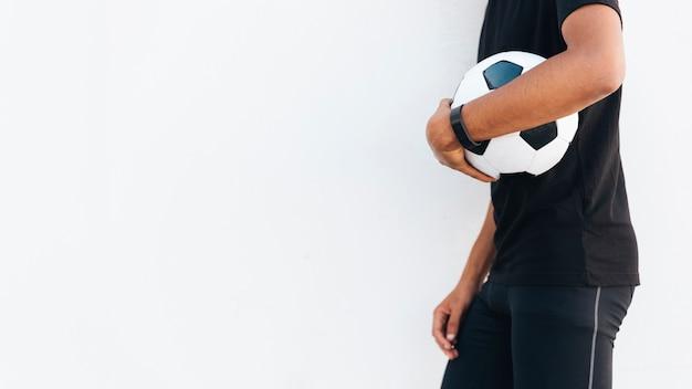 Hombre negro en ropa deportiva con balón de fútbol