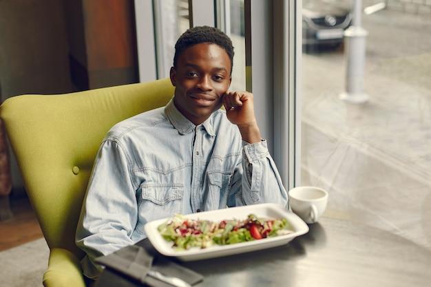Hombre negro sentado en un café y comiendo una ensalada de verduras