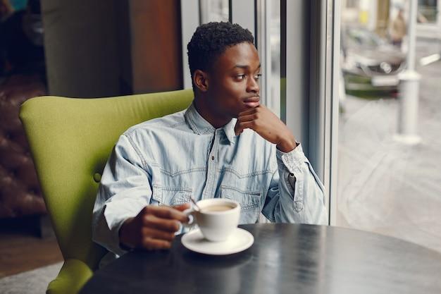 Hombre negro sentado en una cafetería y tomando un café