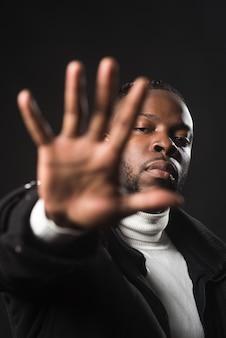 Hombre negro serio diciéndote que te detengas con la mano abierta. de cerca. fondo negro.