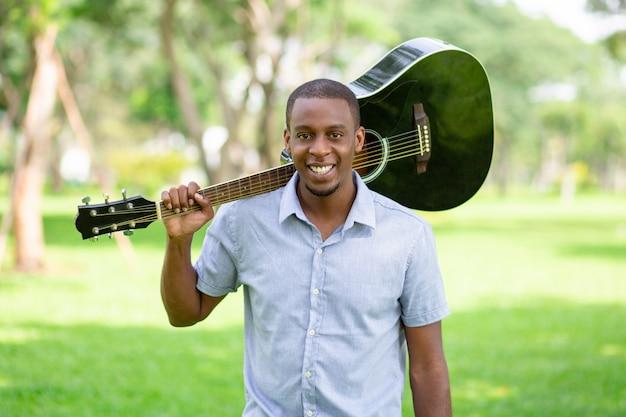 Hombre negro sonriente que sostiene la guitarra en hombro en parque