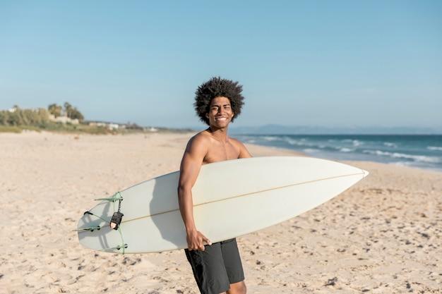 Hombre negro sonriente con tabla de surf en la orilla del mar