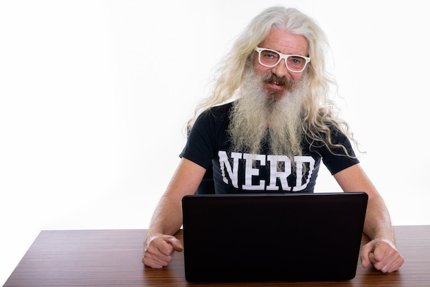 Hombre nerd barbudo senior usando laptop sobre mesa de madera