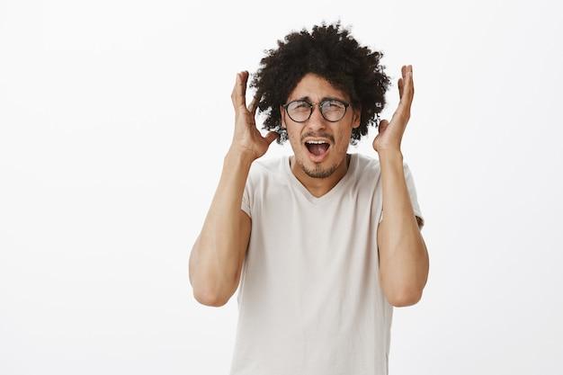 Hombre nerd inseguro en pánico con gafas gritando y estrechándole la mano ansioso