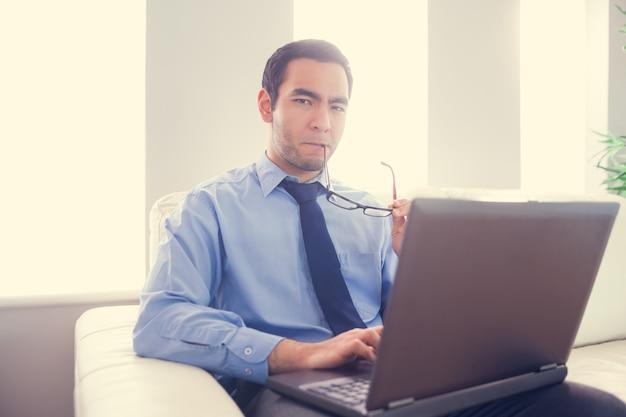 Hombre nervioso mordiendo sus lentes y usando una computadora portátil